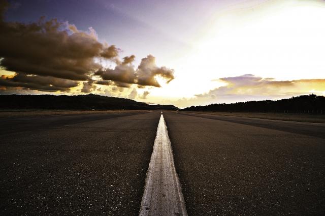 夕空の下、一本の道路が地平線まで伸びている